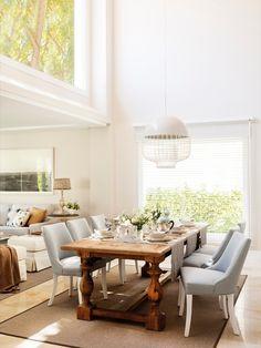 Comedor con techo a doble altura, mesa de madera provenzal, sillas gris piedra, lámpara de techo moderna y grandes ventanales