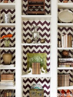 Design tip: Add some visual interest to shelving with graphic wall paper. We love this chevron pattern!