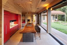 red kitchen punches out from all the wood  love the huge timber slab bench top