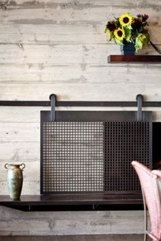 This is one of the most stylish fireplace covers we've ever seen—thanks to barn door hardware.