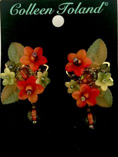 Elegant hand beaded flower earring made with clusters of glass beads and hand painted resin flowers with a glass bead drop. The colors here are an earthy green with a pop of orange. These can be worn with the matching necklace shown on the model or just by themselves. This is a quality piece of jewelry that will last a life time. Created by designer Colleen Toland who has been creating her unique style of vintage jewelry for more than 30 years.  Earrings measure 1.75 inches by 1 inch. All…