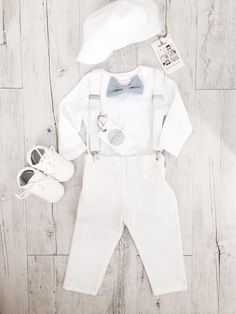 Traditional white with a vintage cool vibe  this baby boys suspenders, onesie, bow tie and pants outfit will stand out at any christening! Super comfortable means your baby will enjoy the special occasion even more.  The regular outfit comes with Long sleeved bodysuit (fastens at crotch), sewn in bowtie, white suspenders and matching white pants (trousers). The additional items of the cap and/or the shoes are available in the drop down menu. Bow tie options are (shown in the photo) L...