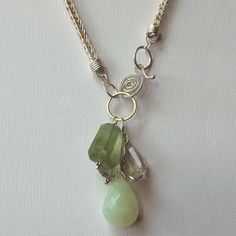 Prehnite gemstone and sterling silver necklace. Handmade sterling silver chain holds a pendant of faceted prehnite, green amethyst and one large faceted teardrop of serpentine. The necklace closes in