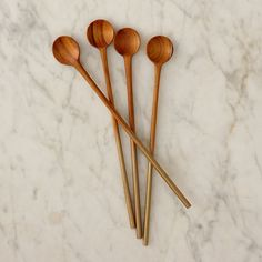 Warm-hued teak and gold-dipped handles add polish to the hors d'oeuvre table with this set of dainty stirrers./