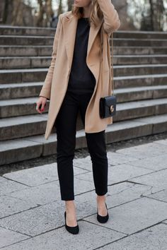 black sweater, pants, and block heels with camel coat