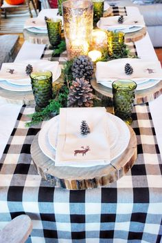 wood chargers + plaid table runner + green glassware + pinecones + tiny evergreens + hurricanes + white dishes + moose napkins = festive + rustic