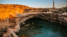 Italy's unique limestone pool, Grotta della Poesia in Roca Vecchia is set on the Adriatic Sea. The natural swimming hole is actually made up of two turquoise and blue karst sinkholes and is an important archaeological site. (Flickr/Giacomo Carena)