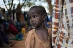 A Somali boy waits for registration into Ifo refugee camp, which is part of the larger Dadaab camp located in Kenya. He joins thousands of other displaced drought victims who wait as long as ten days before becoming fully registered at the camp. - [Phil Moore/AFP/Getty Images]