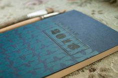 It is an A6 sized planner with handmade screen printed graphics on cover, and printer calendar pages for the next year. It has rounded corners and 128