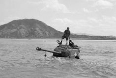 American crewmen stand on their M4A3E8 Sherman stranded trying to ford the Pukhan River, April 7th, 1951. A recovery vehicle pulled it out of the water and the tank and crew were soon back in service.