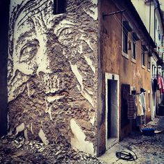 by Vhils using a hammer and chisel in Lisbon.