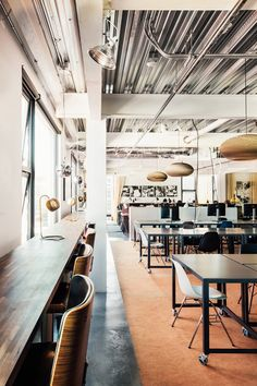 Modern industrial office space with black furniture and warm lighting