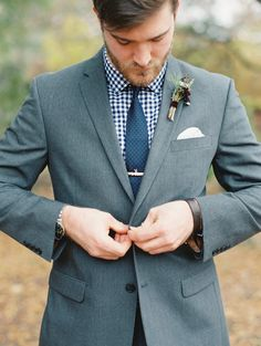 Groom style: Gray suit with navy blue gingham shirt and navy pin dot tie. Image by Landon Jacob at Robert Mills House and Gardens in Columbia, SC.