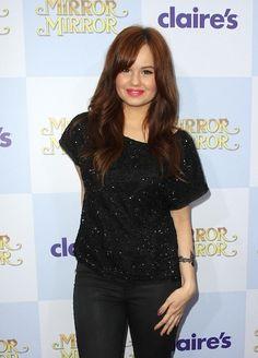 Debby Ryan wears her dark red hair in long soft waves.
