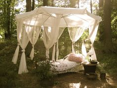 Large outdoor umbrella with soft flowing curtains surrounding a bed (is this by water? because i love lounging near water.  i need a pond.)