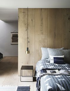 une suspension chevet bi matière en parfaite harmonie avec le mur en planches de bois et la table de chevet minimaliste