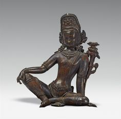 A Nepalese bronze figure of Indra A Nepalese bronze figure of Indra, seated in royal ease, wearing a dhoti, jewellery and a tall headdress, and flanked on one side by a lotus supporting a vajra. Mounted on a modern base. Height 14.3 cm