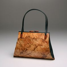 Aristea Handbag Description: European Pepperwood Burl body; Black Obechi top edge detail; Amboyna Burl strap holders and clasp; Leather guss...