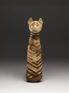 Mummy of a cat with naturalistically modelled head with ears, applied eyes and painted details, the body is covered with light and dark brown narrow linen bandages woven into a herring-bone pattern.