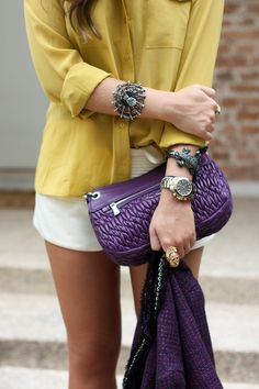 """This mustard yellow button up has never looked so good! Its complementary accessories of the purple haze clutch and chic bracelets, dresses this outfit up to the """"T!"""" The cotton tail shorts draws attention to your legs, so if you're on the shorter side, maybe try pairing this low key outfit with a purple haze  sassy wedge! This will make you appear taller and it will only add it this classy outfit!"""