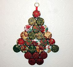LOVE this!  Christmas tree decoration for the wall, made with covered MILK BOTTLE TOPS (I kid you not - could this be any easier?!).  I need more Christmas fabric...