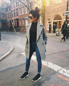 Gray coat. Black high collar shirt. Medium blue skinny jeans. Black lace-up shoes. Sunglasses.