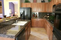 I like the dark countertops with the light wood cabinets, homy and classy :)