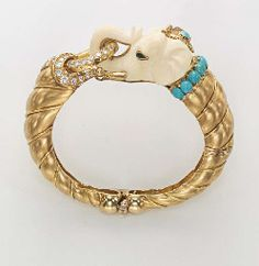 """AN IVORY, GEM-SET AND 18K GOLD """"ELEPHANT"""" BANGLE, BY VAN CLEEF & ARPELS BRACELET RIGIDE """"ELEPHANT"""" IVOIRE, PIERRES DE COULEURS ET OR, PAR VAN CLEEF & ARPELS Designed as a carved ivory elephant head with emerald eye detail, gold tusks, turquoise and diamond headdress with gold tassels and cabochon turquoise collar with pavé-set diamond detail to the brushed 18k gold bangle, made in 1975, 5.5 cm wide Signed VC&A for Van Cleef & Arpels, no. 45444"""