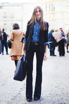 A suit is paired with a denim button-down shirt and a large black leather bag