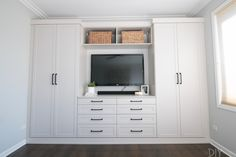 """Master bedroom built-ins with a mounted television """"Morning Dew"""" paint"""