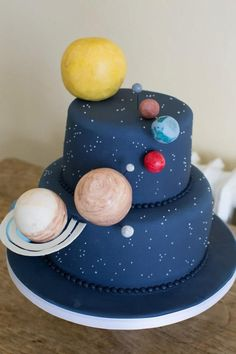 Solar System cake with cake pop planets! We love that Jupiter even has a couple of moons.