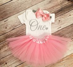 *PLEASE READ SHOP POLICY AND ANNOUNCEMENT FOR CURRENT PRODUCTION AND SHIP TIMES BEFORE PLACING ORDER.*  Let her standout in this beautiful Silver glitter onesie. Made from high quality gold silver heat transfer vinyl. Please leave name you would like in the onesie in the note to seller at checkout. The pink tutu dress is a stretchy to fit newborns and some toddlers. Tulle skirt is about 7.5 long. When relaxed, the waist is about 10 in circumference and will stretch to about 23. Recommended…