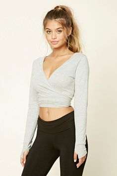 A heathered knit ballet crop top  featuring a wrapped self-tie waist, a deep V-neckline, and long sleeves with thumb holes.