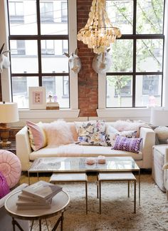 Traditional/contemporary living area, chandelier, white sofa, colorful pillows, large windows, lots of light