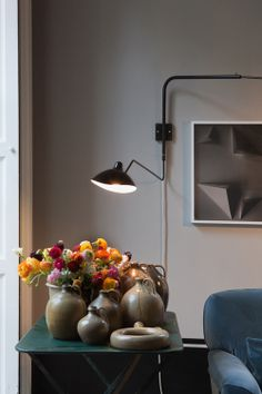 Warm grey walls; cluster of neutral pottery; serge mouille wall lamp