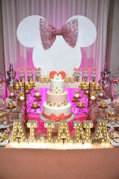 Pink and Gold Minnie Mouse dessert table with white Minnie silhouette, gold marquee letters, cake pops, and much more.