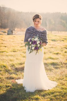 David's Bridal bride Caitlin layered a cozy knit wrap over her strapless lace and tulle wedding dress for her Fall farm wedding. Photo by: Trish Kemp Photography