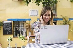Young female tourist looking at laptop at sidewalk cafe, Valencia, Spain