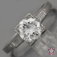 This Art Deco Engagement Ring original in solid Platinum weighs 2.6g and measures 6mm wide and 5mm deep. Centrally prong-set in an aesthetic geometric ninety degree square prong-setting, this Antique Diamond Engagement Ring boasts a high quality EGL Certified 0.88ct round brilliant-cut diamond graded E-F color and VVS2-VS1 clarity measuring 6.10mm in diameter (EGL Cert.# 60729604D). In snag-free, streamline construction, this unique Art Deco Antique Engagement Ring is shoulder accentuated…