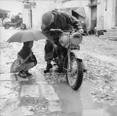 A little girl holding an umbrella watches a despatch rider attempt to clear the carburettor of his motorcycle in torrential rain, 4th October 1943.