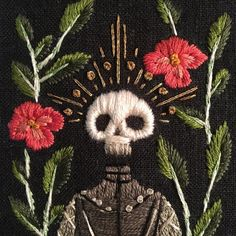Embroidery of illuminated skull with flowers on black ground by Kate Walsh. (Memento Mori)