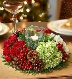 red and white roses, green hydrangeas and assorted Christmas greens accented by hypericum berries and pinecones.