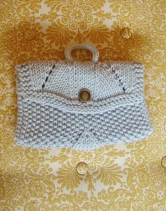 """Free knitting pattern for Sundance Make Up Bag. Joëlle Meier Rioux this adorable bitty bag with cute details that is 7"""" wide x 4½"""" tall"""