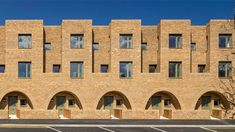 Peter Barber Architects has completed terraced houses in London's Stratford, featuring a monolithic brick facade punctuated by recessed arches and balconies