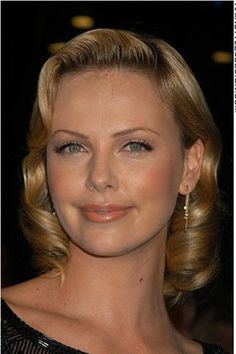 This classy look is straight out of the movies. Charlize Theron is seen here with a retro 50's hairstyle. The hair has lots of volume as it is curly. Tucked back behind at one ear and left loose at the other, this is such a romantic style.The cut is medium length.Charlize has a gorgeous golden blonde hair colouring. This colour is perfect for her skin tone.