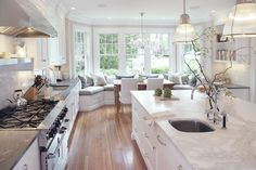 Gorgeous kitchen with bay windows and built-in window seats with blue and gray pillows.
