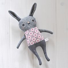 Geneviève is a sweet one-of-a-kind handcrafted bunny featuring hand-painted  and hand-embroidered details. Geneviève wears a removable cotton collar and  arrives in our classic reusable cotton drawstring bag that is ideal for  gift giving.  - Dusky indigo colored cotton face and arms - Orchid & navy floral print body / charcoal striped cotton legs - Hand-painted and hand-embroidered details - Measures approx. 11in / 28cm (from head to toe - not including ears) - One-of-a-kind - Geneviève is…
