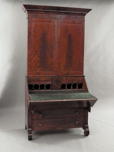 A Good American Late Classical Carved Mahogany Secretary/Bookcase, mid-19th c., probably Southern, in two parts, the upper paneled doors opening to adjustable serpentine shelves, distinctive fold-down desk reveals a fitted interior with center door of Gothic design flanked by drawers and eight Gothic arched pigeonholes; the lower section having four drawers flanked by columnar pilasters supported on scroll feet, height 101 1/2 in., width 55 in., depth 39 in.