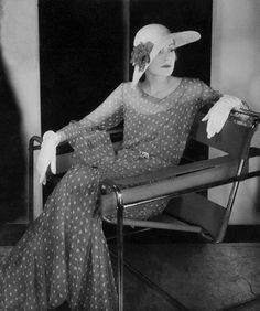 A model sporting a diaphanous Chanel dress as she sits on a Le Corbusier chair.