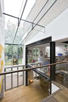 A modern double height frameless glass infill extension with aluminium bifold doors and glass beams.